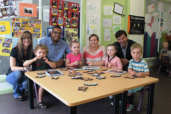 L-R Centre Director Jo Mavrigiannakis, parent Sam Khalil, Early Childhood Teacher Melissa-Rae Oakley and Angus Taylor, with children Rhys Brooker, Phoebe Dalley, Shelby Smyth and Harper Tarplee practising on their ipads before the language trial begins next year.